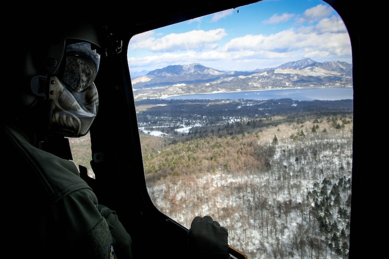 Tech. Sgt. Michael Wright, 459th Airlift Squadron special mission aviator evaluator, looks out the window of a UH-1N Iroquois to ensure the surrounding area is clear from other aircraft near Mt. Fuji, Japan, Jan. 13, 2017. The aircrew and pilots continuously check their surroundings as they follow the visual flight rules to ensure the safety of the aircrew and aircraft. (U.S. Air Force photo by Staff Sgt. David Owsianka)