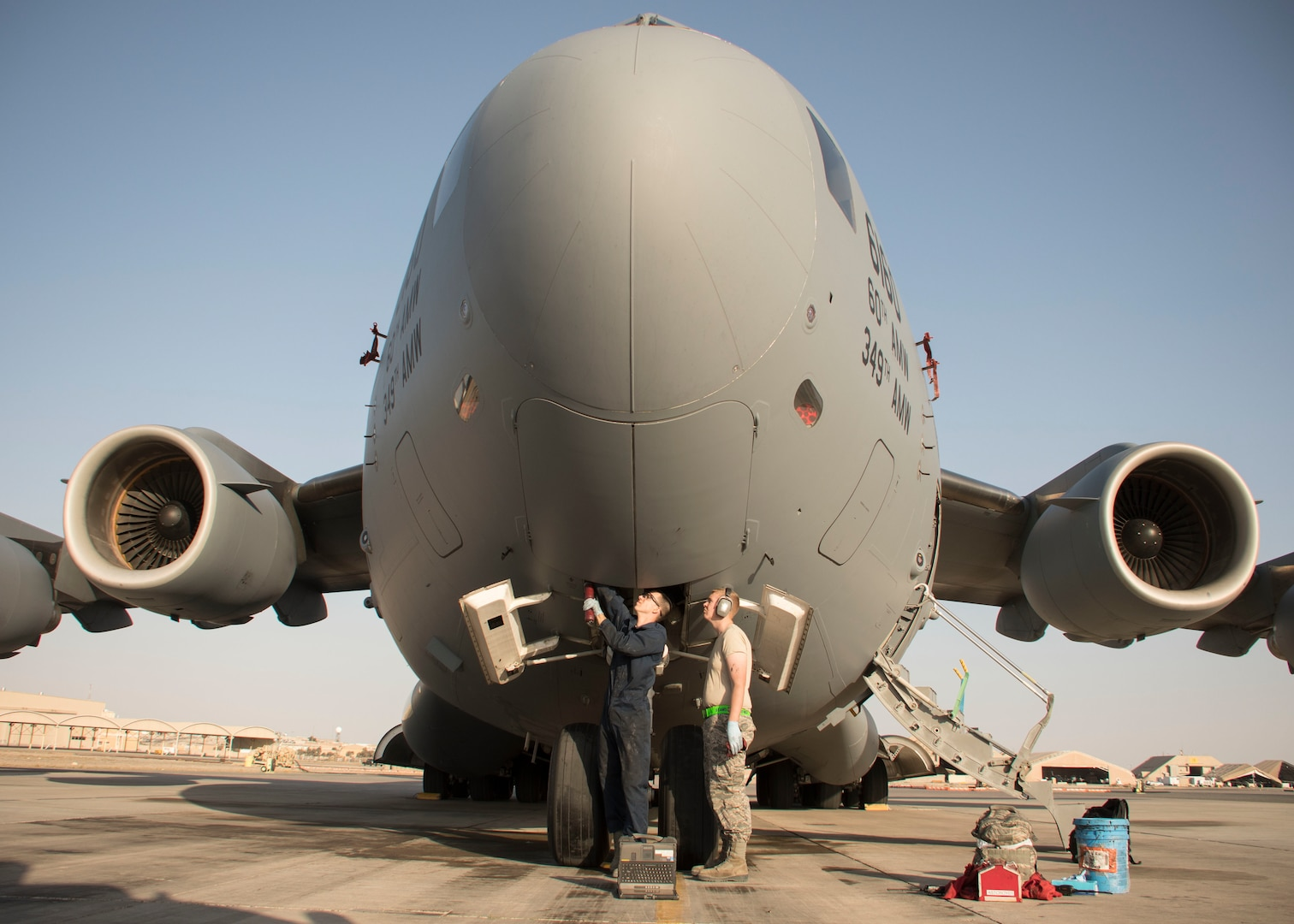 Two Airmen from the 5th Expeditionary Air Mobility Squadron, grease points on the nose landing gear of a C-17 Globemaster III during a post-flight inspection at an undisclosed location in Southwest Asia Jan. 13, 2017. The squadron flies an average of 2,500 sorties a year, moving 180,000 personnel and 80,000 tons of cargo. (U.S. Air Force photo/Senior Airman Andrew Park)