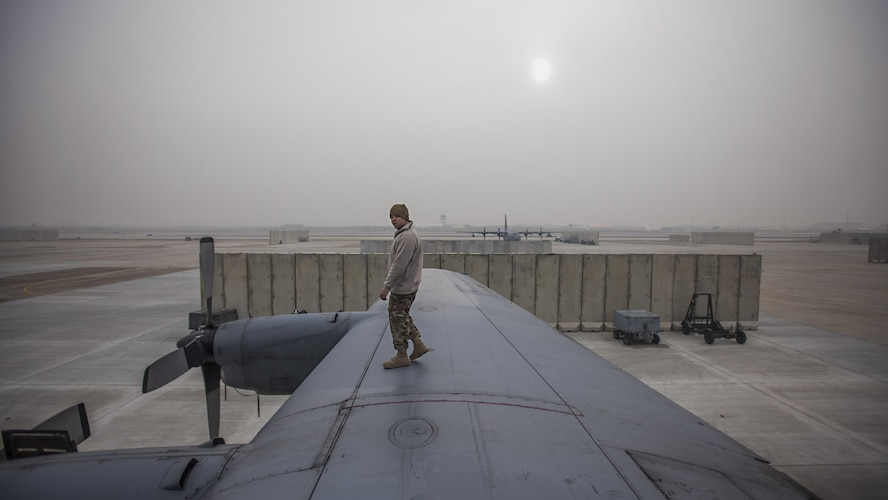 Staff Sgt. Sean Nelson, 455th Expeditionary Aircraft Maintenance Squadron crew chief, walks along the wing of an EC-130 Compass Call Jan. 18, 2017 at Bagram Airfield, Afghanistan. In the past four months, the unit has flown more than any other time of the same period in the history of the unit. (U.S. Air Force photo by Staff Sgt. Katherine Spessa)