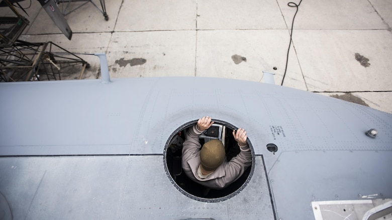 Staff Sgt. Sean Nelson, 455th Expeditionary Aircraft Maintenance Squadron crew chief, lowers himself off the roof of an EC-130 Compass Call Jan. 18, 2017 at Bagram Airfield, Afghanistan. The aircraft's communications jamming capability is an indispensable asset to ground forces and has led to 2,193 terrorists removed from the battlefield, just since 2014. (U.S. Air Force photo by Staff Sgt. Katherine Spessa)