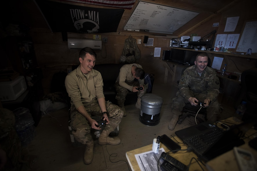 Senior Airman Domynic Panto and Tech. Sgt. Bob Kaster, 455th Expeditionary Aircraft Maintenance Squadron C-130 Compass Call Aircraft Maintenance Unit communications navigations and mission systems technicians, and Airman 1st Class Mitchell Dillon, 455th EAMXS C-130 AMU electronic warfare combat systems technician, play video games at Bagram Airfield, Afghanistan Jan. 12, 2017. When they're not working out on the flightline, members of the AMU play sports or video games and work out together. (U.S. Air Force photo by Staff Sgt. Katherine Spessa)