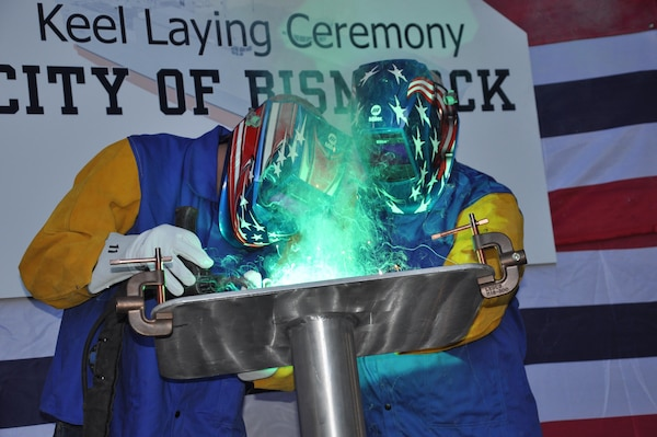 The Honorable Robert O. Wefald (right), former North Dakota State District Court Judge, welds his initials into the keel plate of the future USNS City of Bismarck (EPF 9) with the assistance of Austal USA Class A Welder Richard A. Sinclair (left). The keel authentication ceremony was held Jan. 18 at the Austal USA Shipyard in Mobile, Ala.