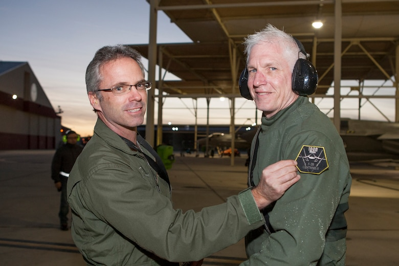 "Robert Wallace (left), Lockheed Martin Flight Operations senior manager, presents David ""Doc"" Nelson a special flight suit patch for being the first to achieve 1,000 flight hours in the F-35 Joint Strike Fighter Jan. 6. (Courtesy photo by Tom Reynolds/Lockheed Martin)"