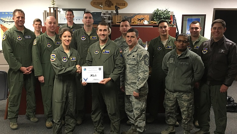 "Capt. Steven Parsons, 47th Student Training Squadron assistant director of operations flight examiner (front center), accepts the ""XLer of the Week"" award from Col. Michelle Pryor, 47th Flying Training Wing vice commander (front left), and Chief Master Sgt. George Richey, 47th FTW command chief (front right), on Laughlin Air Force Base, Texas, Jan. 11, 2017. The XLer is a weekly award chosen by wing leadership and is presented to those who consistently make outstanding contributions to their unit and Laughlin. (U.S. Air Force photo/Airman 1st Class Benjamin N. Valmoja)"