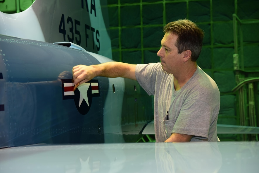 Neil Orlowski, a Corrosion Control Specialist in the 12th Maintenance Group, applies a decal to a T-38C Talon at Joint Base San Antonio-Randolph, Texas, Jan. 13, 2017.  Members of the corrosion control shop are changing the plane's color scheme from two-tone gray to heritage blue, a scheme that was used by the 435th Fighter Training Squadron 40 years ago, ahead of a reunion of pilots that trained for fighter fundamentals after Jan. 1, 1977. (U.S. Air Force photo/Randy Martin)