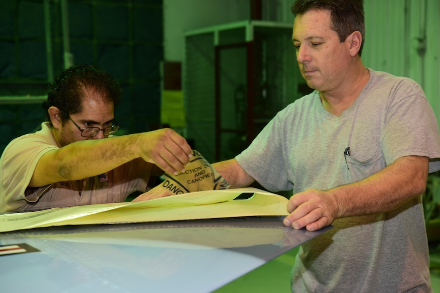 Marion Tarin and Neil Orlowski, both Corrosion Control Specialists in the 12th Maintenance Group, prepare a decal for application paint to a T-38C Talon at Joint Base San Antonio-Randolph, Texas, Jan. 13, 2017. Members of the corrosion control shop are changing the plane's color scheme from two-tone gray to heritage blue, a scheme that was used by the 435th Fighter Training Squadron 40 years ago, ahead of a reunion of pilots that trained for fighter fundamentals after Jan. 1, 1977. (U.S. Air Force photo/Randy Martin)