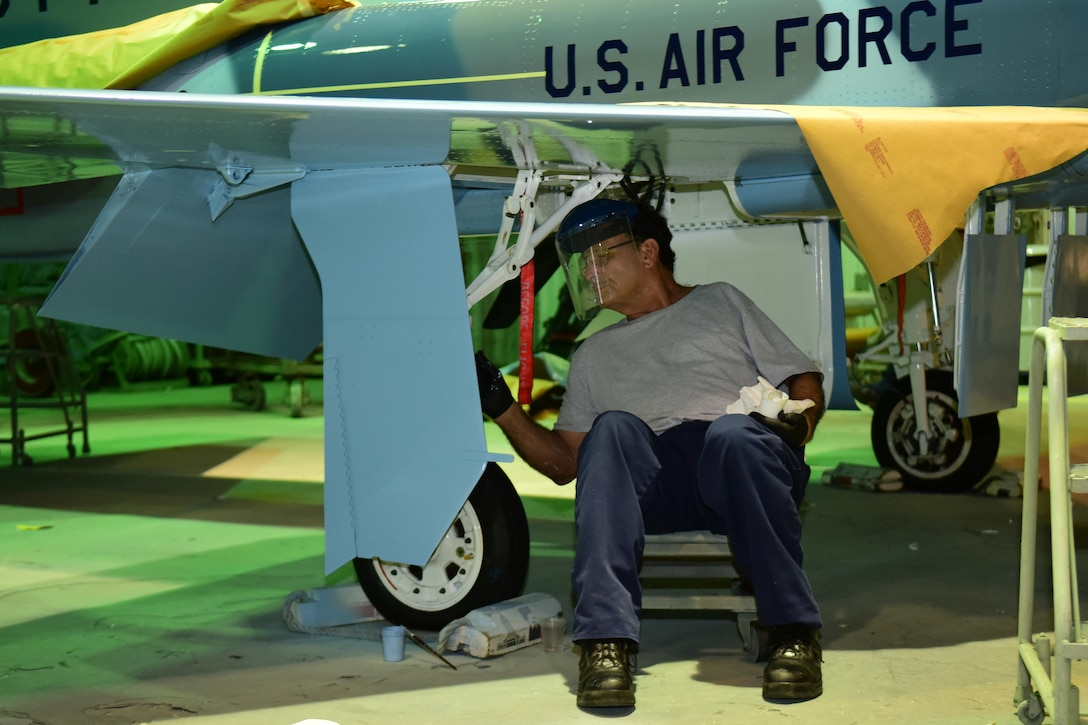 Rudy Olivarez, a Corrosion Control Specialist in the 12th Maintenance Group, applies paint to the landing gear of a T-38C Talon at Joint Base San Antonio-Randolph, Texas, Jan. 13, 2017.  Members of the corrosion control shop are changing the plane's color scheme from two-tone gray to heritage blue, a scheme that was used by the 435th Fighter Training Squadron 40 years ago, ahead of a reunion of pilots that trained for fighter fundamentals after Jan. 1, 1977. (U.S. Air Force photo/Randy Martin)