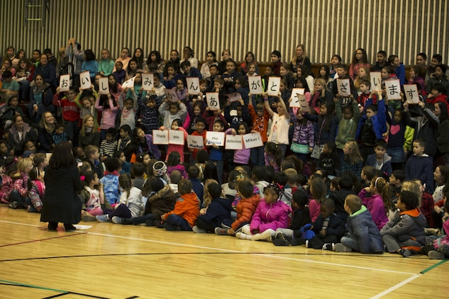 """Matthew C. Perry Elementary School students hold up signs at the seventh annual mikan presentation at Marine Corps Air Station Iwakuni, Japan, Jan. 19, 2017. The host nation class's signs read """"Thank you for the delicious mikans!"""" in Japanese, English and Spanish. Local farmers presented the sweet, easy-to-peel citrus fruit, which is similar to Mandarin oranges, to students expanding their experience of Japanese cultures. (U.S. Marine Corps photo by Lance Cpl. Gabriela Garcia-Herrera)"""