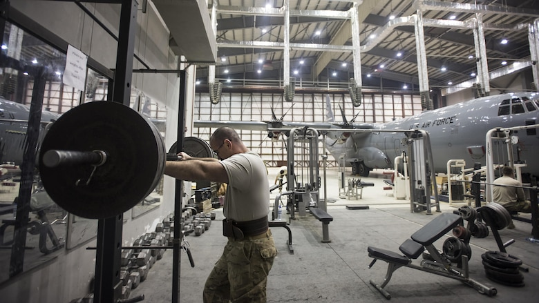 Tech. Sgt. Jason Caswell, 455th Expeditionary Aircraft Maintenance Squadron C-130 Hercules debrief NCO-in-charge, prepares to lift weights Jan. 4, 2017 at Bagram Airfield, Afghanistan. Caswell is a wounded warrior deployed on his second back-to-back tour, his first time downrange since losing a leg to a sports injury. (U.S. Air Force photo by Staff Sgt. Katherine Spessa)