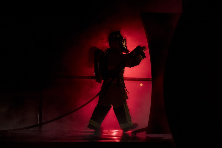 A firefighter enters a prop aircraft during nighttime, live-fire training Jan. 10, 2017, at Moody Air Force Base, Ga. After extinguishing external fires, firefighters entered the prop aircraft to continue combating the flames. (U.S. Air Force photo/Airman 1st Class Daniel Snider)