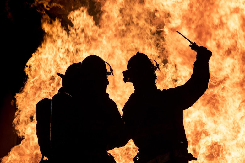 Firefighters from the 23rd Civil Engineer Squadron signal for a radio check prior to advancing on a fire during nighttime, live-fire training Jan. 10, 2017, at Moody Air Force Base, Ga. The training is an annual requirement for Moody AFB firefighters and is just one of the ways they stay ready to protect people, property and the environment from fires and disasters. (U.S. Air Force photo/Staff Sgt. Ryan Callaghan)