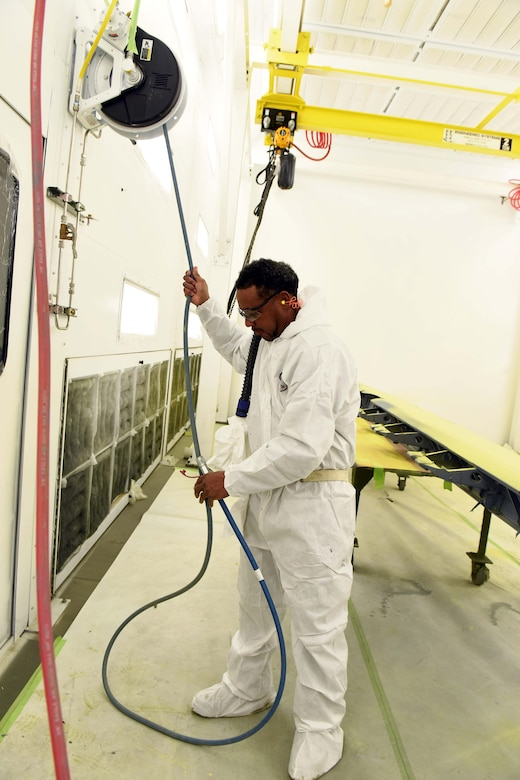 Rivers Foreman, 571st Commodities Maintenance Group aircraft painter, paints a C-130 aileron inside a recently installed state-of-the-art paint booth. Installation of three new paint booths at the facility has drastically decreased production time, work hazards, health hazards and environmental impact simultaneously. (U.S. Air Force photo by Tommie Horton)