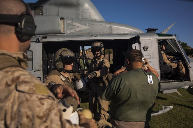 Two UH-1Y crew chiefs with Marine Aviation Weapons and Tactics Squadron One offload personnel at Kiwanis Park in Yuma, Ariz. during a Humanitarian Assistance/Disaster Relief (HA/DR) Exercise, part of the Weapons and Tactics Instructor Course 1-17, Friday, October 14, 2016.