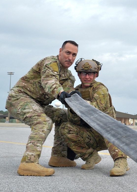 Master Sgt. James Albanesi, the team chief for the forward area refueling point program with the 1st Special Operations Logistics Readiness Squadron, assists a student as they anchor a fuel hose during a class demonstration at Hurlburt Field, Fla., Jan. 10, 2017. A fuel hose is anchored by Airmen to ensure little movement while a squeegee, a metal tool with two rolling pin like devices, is used to push residual fuel back into an aircraft to save space and reduce risk of leaks or spillage. The FARP program is a United States Special Operations Command initiative that trains petroleum, oils and lubrication Airmen to perform covert, nighttime refueling operations in deployed locations where fueling points are not accessible or when air-to-air refueling is not possible. (U.S. Air Force photo by Senior Airman Andrea Posey)