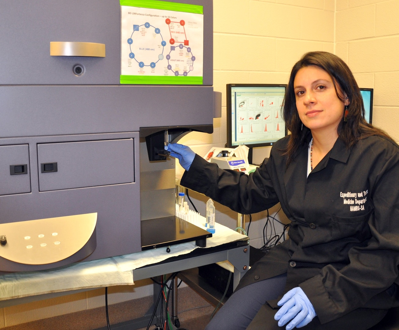Dr. R. Madelaine Paredes, a researcher in Naval Medical Research Unit San Antonio's Immunodiagnostic and Bioassay Development Department, demonstrates the use of the flow cytometer technique to perform single cell measurements. Flow cytometer can identify the numbers of cells that have a particular feature (size, or a specific marker in their surface or intracellular). Navy researchers can then discern what molecules are being produced by each cell type and compile an extensive inflammatory profile for that particular sample.