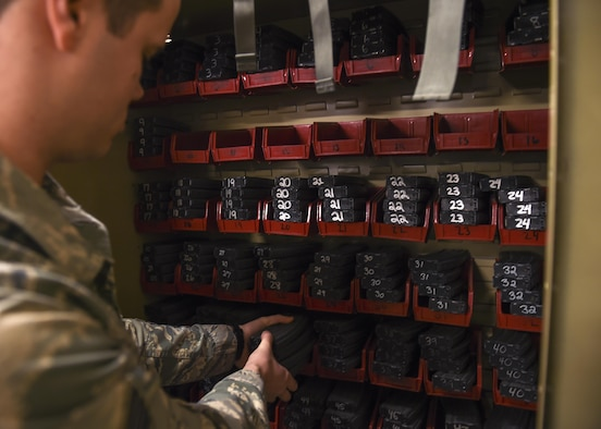 U.S. Air Force Staff Sgt. Ryan Quade, 19th Security Forces Squadron NCO in charge of the armory, grabs M4 assault rifle magazines to arm up Defenders Jan. 17, 2017, at Little Rock Air Force Base, Ark. Each day, Quade's team conducts inventory of all weapons, radios and associated equipment in the armory prior to issuing any weapons or equipment. (U.S. Air Force photo/Senior Airman Harry Brexel)