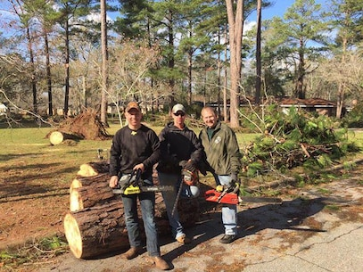 Marines pose with Darrel Ealum, a retired Marine major and current Georgia State Representative, after cutting up trees and removing debris from severe storms that swept through the city of Albany, Ga., and surrounding counties, Jan. 7.