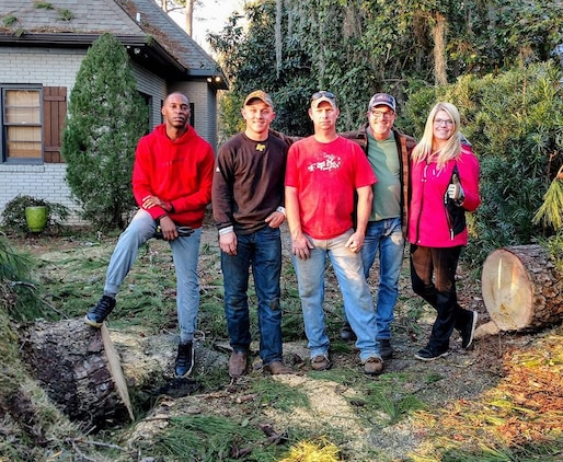 Marines pose for a photo with Jerry Usry, a community volunteer, after cutting down a pine tree that had fallen during a recent severe storm, Jan. 7