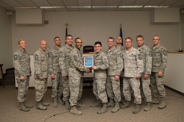 Airman 1st Class Ernest Trueblood, a 49th Wing Judge Advocate paralegal, receives the January Chief's Choice Award, from Chief Master Sgt. Barrington Bartlett, the 49th Wing command chief Jan. 19, 2017, at Holloman Air Force Base, N.M. (U.S. Air Force photo by Tech. Sgt. Amanda Junk)