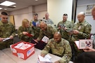 Army Reserve Soldiers assigned to the 85th Support Command read through a box of 'Thank You' letters sent from a local elementary school, Jan. 8, 2017. More than 170 letters were sent with personal 'Thank Yous' and drawings of the student's family members, Soldiers, and first responders. 