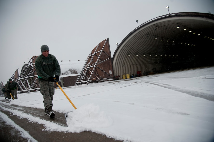 """U.S. Air Force Senior Airman Joshua Johnston, 25th Aircraft Maintenance Unit avionics system technician, shovels snow in front of an aircraft hangar on Osan Air Base, Republic of Korea, Jan. 20, 2017. The 25th AMU removed snow in front of their hangers to keep the A-10 Thunderbolt II """"ready to fight tonight"""". (U.S. Air Force photo by Staff Sgt. Jonathan Steffen)"""