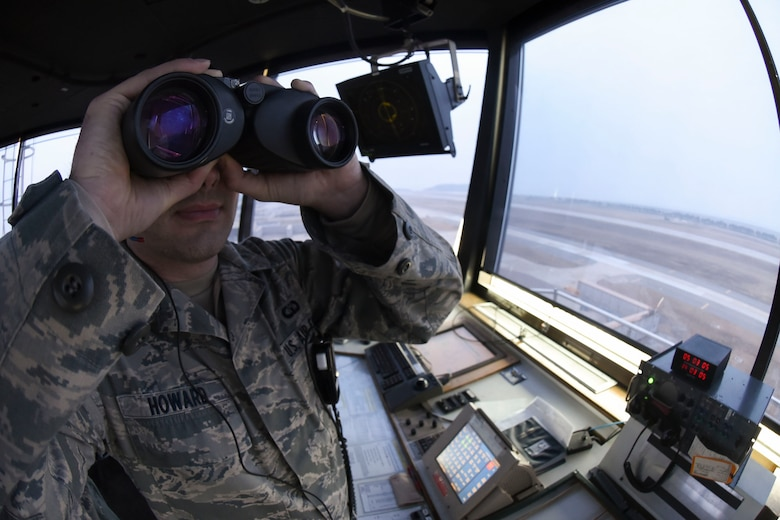 Staff Sgt. Jeffery Howard, 8th Operations Support Squadron air traffic controller, looks at the runway through his binoculars at Kunsan Air Base, Republic of Korea, Jan. 5, 2017. Howard ensures the runway is clear from any hazards to aircraft. (U.S. Air Force photo by Senior Airman Michael Hunsaker/Released)