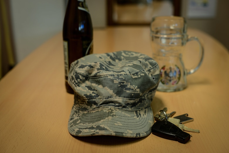 A crumpled Airman Battle Uniform cap lies on a table next to a key set, beer bottle, and beer mug at Ramstein Air Base, Germany, Jan. 20, 2017. The Airman Against Drunk Driving program is available at many Air Force Bases and aims to prevent cases of DUI among Airmen. (U.S. Force photo by Airman 1st Class Joshua Magbanua)