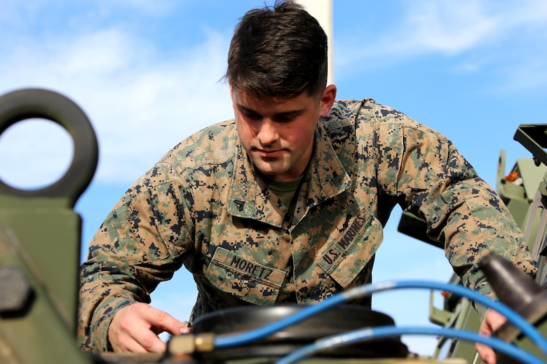 Cpl. Jimmy Moretz inspects the engine of an MK28 extended cargo truck aboard Marine Corps Air Station Cherry Point, N.C., Jan. 17, 2017. Moretz is the emergency dispatcher assigned to Marine Air Support Squadron 1, Marine Air Control Group 28, 2nd Marine Aircraft Wing, and training noncommissioned officer for his platoon in the motor and transport section of the squadron. Moretz has been recognized as the noncommissioned officer of the quarter for the period of Oct. 1, 2016 to Dec. 31, 2016 for his outstanding work in his squadron. (U.S. Marine Corps photo by Cpl. Jason Jimenez/ Released)