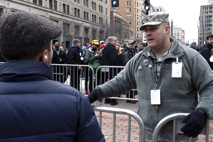 Army Sgt. Kurtis Brown, a military police officer with the South Dakota Army National Guard's 235th Military Police Company, answers questions from a spectator near a checkpoint in Washington, D.C., during the 58th Presidential Inauguration, Jan. 20, 2017. Brown was one of more than 7,500 National Guard members from 44 states, territories and the District of Columbia, who supported local authorities during the inauguration.