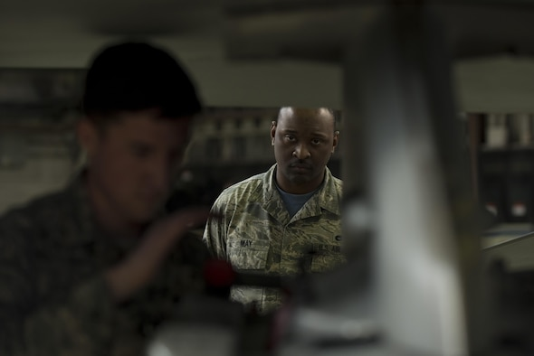 Staff Sgt. Kiefer May, 52nd Maintenance Group squadron lead crew member, center, evaluates Airman 1st Class John Gaddis, 52nd Aircraft Maintenance Squadron tactical aircraft weapons system specialist, left, during the annual weapons load competition in Hangar One at Spangdahlem Air Base, Germany, Jan. 20, 2017. The competition, consisting of two competing teams, was scored for safety and reliability, but speed and technical accuracy played a major role in scoring points to become the wing's best load crew. Winners will be announced at the Maintenance Professional of the Year banquet here March 10, 2017. (U.S. Air Force photo by Airman 1st Class Preston Cherry)