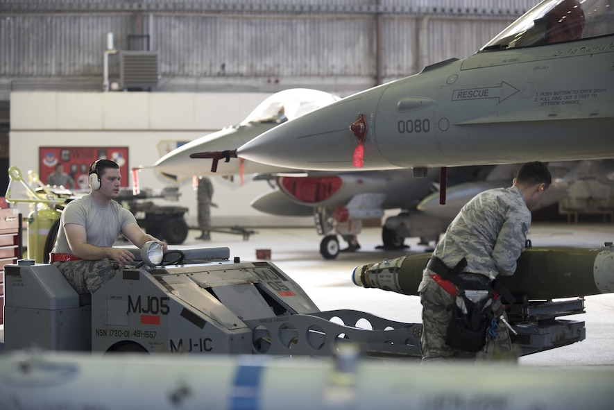 Airman 1st Class Christian Edson, 52nd Aircraft Maintenance Squadron tactical aircraft weapons system specialist, left, and Staff Sgt. Daniel Vazquez, 52nd Aircraft Maintenance Squadron weapons load crew chief, right, prepare to load an inert weapon on an F-16 Fighting Falcon during the annual weapons load competition in Hangar One at Spangdahlem Air Base, Germany, Jan. 20, 2017. The competition, consisting of two competing teams, was scored for safety and reliability, but speed and technical accuracy played a major role in scoring points. Winners from the competition will be announced at the Maintenance Professional of the Year banquet March 10, 2017. (U.S. Air Force photo by Airman 1st Class Preston Cherry)