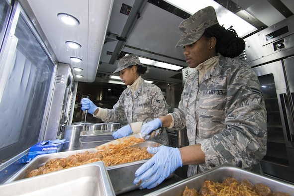 U.S. Air Force Airman 1st Class Ambrasia Washington, right, and Kayla Akers from the 116th Air Control Wing (ACW) Services Flight, Georgia Air National Guard (ANG), prepare trays of spaghetti during dinner preparation for joint-forces personnel supporting the 58th Presidential Inauguration, Washington, D.C., January 18, 2017. A team of 10 Airmen from the 116th ACW deployed with their Disaster Relief Mobile Kitchen Trailer (DRMKT).  Working from FedEx Field, home to the Washington Redskins, the team worked along side services teams from other ANG units across the nation preparing and serving meals to about 3,500 joint-force members per day deployed to the National Capital Region. In all, about 7,500 National Guard Soldiers and Airmen, from 44 states, three territories and the District of Columbia, served with the specially created Joint Task Force – District of Columbia. As a whole, National Guard Soldiers and Airmen augmented the U.S. Secret Service, U.S. Capitol Police and D.C. Metropolitan Police forces on a range of support including traffic control, crowd management, logistics and communication. (U.S. Air National Guard photo by Senior Master Sgt. Roger Parsons)