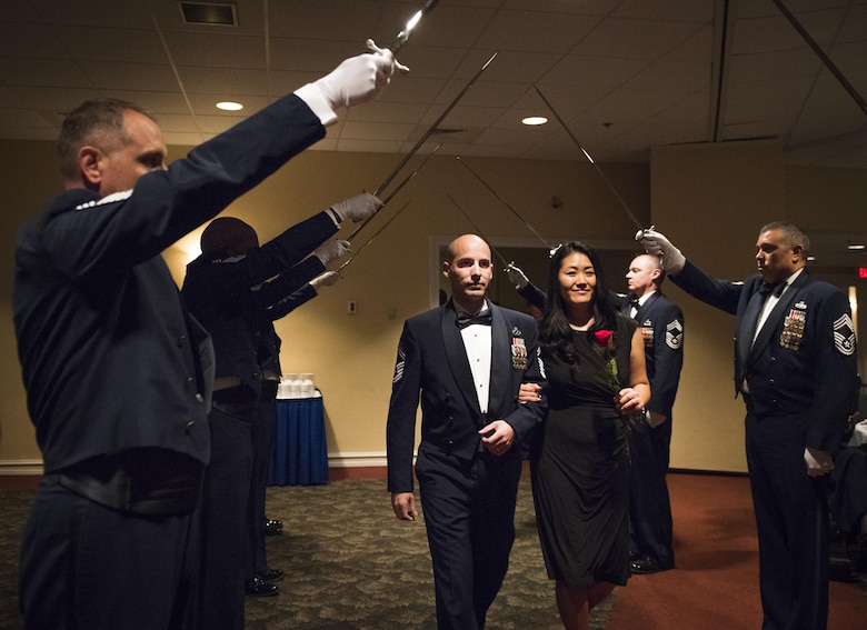 Senior Master Sgt. Mark Duarte, 359th Training Squadron, and his spouse walk beneath the saber cordon at the beginning of the recognition ceremony Jan. 20 at Eglin Air Force Base, Fla.  Six new chiefs were recognized during the formal ceremony and dinner.  (U.S. Air Force photo/Samuel King Jr.)