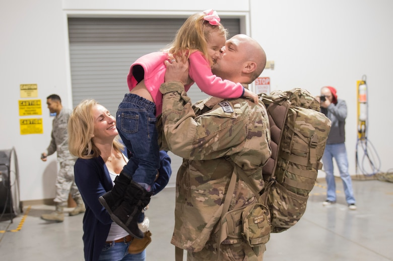Capt. Jacob Becker, 921st Contingency Response Squadron airfield operations officer, hugs and kiss his daughter as he returns from a three-month deployment to Iraq, in support of Operation Inherent Resolve, Jan. 14, 2017, at Travis Air Force Base, California.  The CRW played a crucial role in reopening Qayyarah West Airfield and moving more than 1,423 short tons of cargo in and out of the region. (U.S. Air Force Photo by Tech. Sgt. Liliana Moreno)
