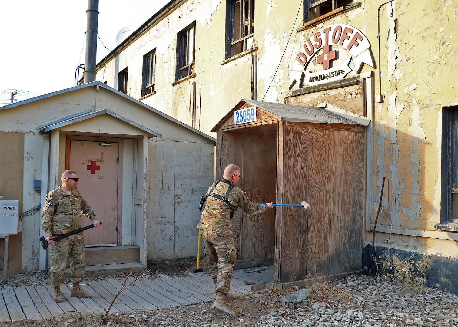 """The Commander of the 1st Combat Aviation Brigade Col. John M. Cyrulik stands at the ready waiting to take a swing with his sledge hammer to the old MEDVAC facility.  The 389th Engineer Company, 368th Engineer Battalion, 176th Engineer Brigade, built a new MEDVAC facility which will house members of Charlie Company, 2nd Battalion, 1st Aviation Regiment (General Support Aviation Battalion) from Ft. Riley, Kan. (""""Boomer Dust-off""""). (DOD photo by Jet Fabara)"""