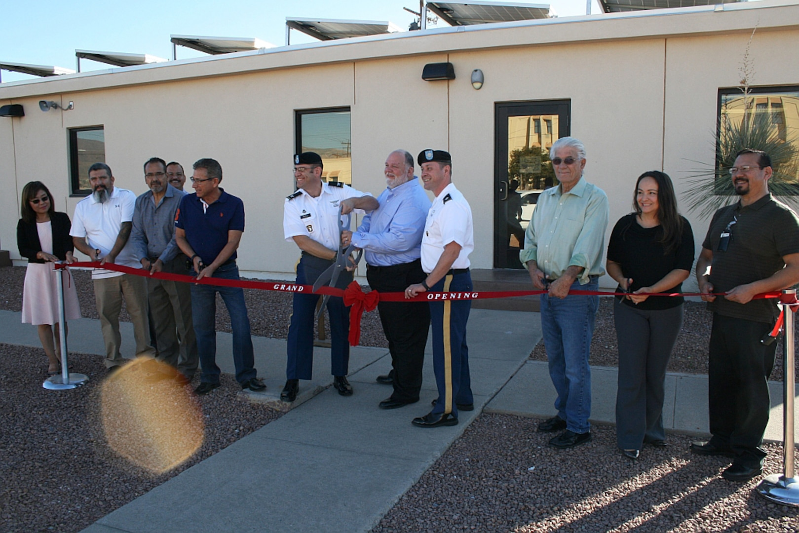 Army Col. Robert J. Miceli, Defense Contract Management Agency Phoenix commander; and Keith L. Duncan, DCMA Albuquerque - El Paso quality assurance team leader, cut the ribbon for the agency's new Fort Bliss office facility. Members of the DCMA El Paso team assisted in the ceremony and celebrated the grand opening of the new office space. From left, Kim Birch, Homero U. Ramos, Eduardo Luera, Jesus Barrios, José G. Arrieta, Miceli, Duncan, Army Lt. Col.  John S. Pires, James D. Avant, Maria Ludwig and Alex Luna. (DCMA photo by Jay Maitland, DCMA Albuquerque - El Paso)