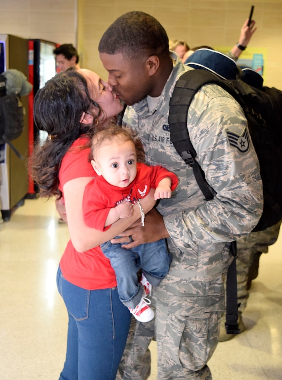 Staff Sgt. Barrett Cain III, 433rd Security Forces Squadron, greats his wife, Krystal and his son, Cain IV, upon his return Jan. 19, 2017 at the San Antonio International Airport, Texas. Thirteen Citizen Airmen returned from a six-month deployment to Southwest Asia in support of Operation Inherent Resolve.