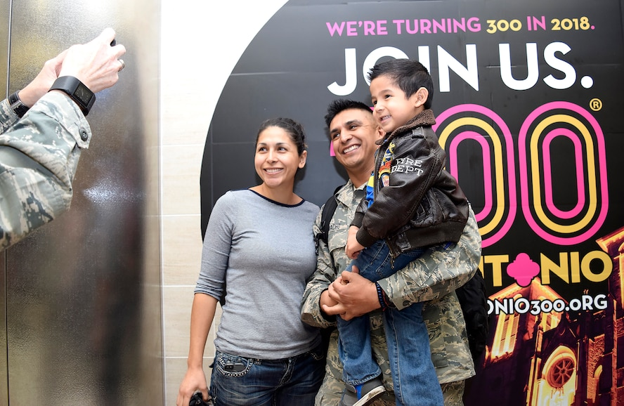 Master Sgt. Manuel Camacho, Jr., 433rd Security Forces Squadron, takes a moment with his son Adrian and SMSgt. Elena Ramirez, 433rd Aerospace Medicine Squadron upon his return Jan. 19, 2017 at the San Antonio International Airport, Texas. Thirteen Citizen Airmen returned from a six-month deployment to Southwest Asia in support of Operation Inherent Resolve.