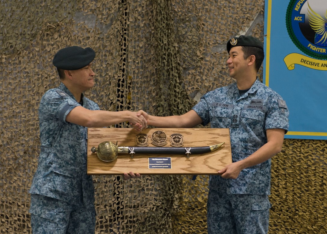 Republic of Singapore Air Force Senior Lt. Col. Tham Yeow Min passes a sword and the position of senior-ranking officer to Lt. Col. Oon Kok Choon, during a change of assignment ceremony at Mountain Home Air Force Base, Idaho, Jan. 17, 2017. Tham has been the SRO and Peace Carvin V Detachment Commander since June 2013. (U.S. Air Force photo by Airman 1st Class Chester Mientkiewicz/Released)