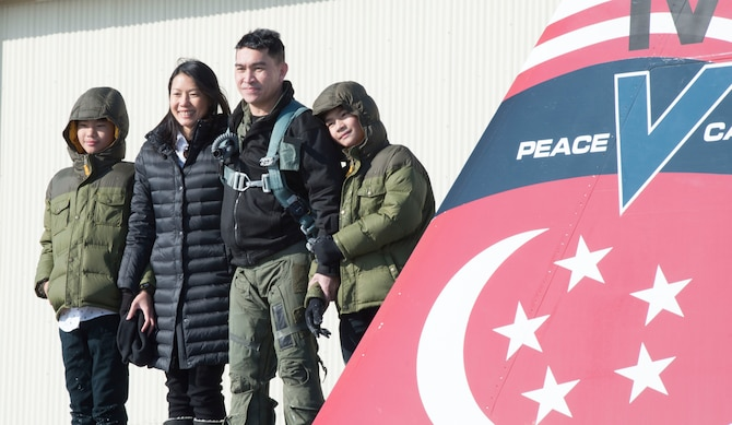 Republic of Singapore Air Force Senior Lieutenant Colonel Tham Yeow Min, 428th Fighter Squadron senior-ranking officer, poses with his family on the 428th flagship, Jan. 17, 2017, at Mountain Home Air Force Base, Idaho. Tham handed command over to Lieutenant Colonel Oon Kok Choon at the Peace Carvin V change of assignment and appointment parade. (U.S. Air Force photo by Senior Airman Malissa Lott/Released)