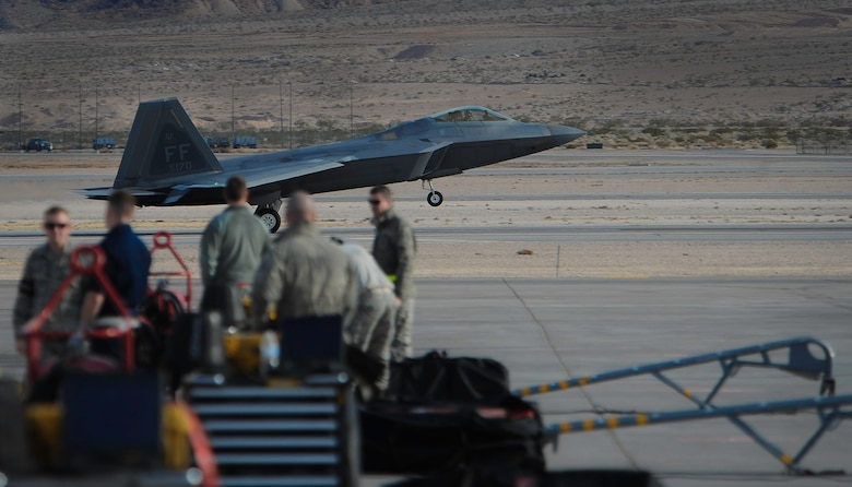 An F-22 Raptor assigned to the 1st Fighter Wing, Joint Base Langley-Eustis, Va., lands as maintainers wait for the fighter to taxi before Red Flag 17-1 on Nellis Air Force Base, Nev., Jan. 18, 2017. All four branches of the U.S. Military and air forces from allied nations participate in Red Flag. (U.S. Air Force photo by Airman 1st Class Kevin Tanenbaum/Released)