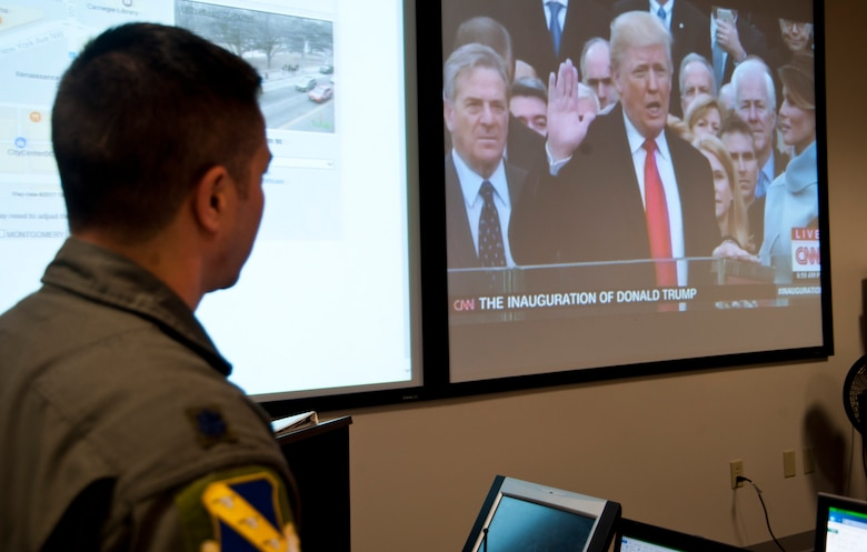 Lt. Col. David Fink, 11th Wing command post director, watches a live broadcast from Joint Base Andrews, Md., Jan. 20, 2017, of president elect Donald Trump taking the oath of office. Fink and approximately 20 other representatives from Team Andrews formed a crisis action team to monitor and coordinate Air Force personnel participating in the presidential inauguration ceremony and parade. (U.S. Air Force photo by Staff Sgt. Joe Yanik)