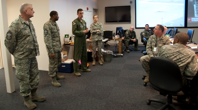 Maj. John Alsbrooks (third from left), 11th Wing's crisis action team director, updates fellow team members at Joint Base Andrews, Md., Jan. 20, 2017, about the status of the Airmen participating in the 58th Presidential Inauguration parade and ceremony. The CAT comprised approximately 20 representatives from every major mission partner within JBA. (U.S. Air Force photo by Staff Sgt. Joe Yanik)