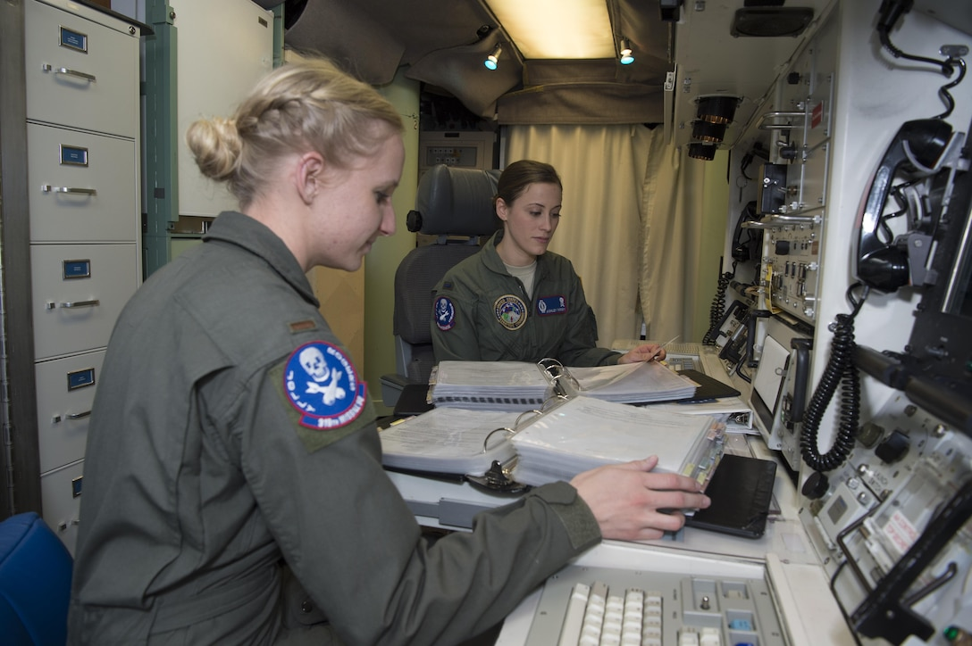 First Lt. Ashley Mirsky, 319th Missile Squadron missile combat crew commander, and 2nd Lt. Marie Blair, 319th MS deputy missile combat crew commander, run through a checklist in a launch control center in the 90th Missile Wing missile complex, Dec. 19, 2016. The crew has been paired together for four months and continuously challenges each other on their weapons system knowledge. (U.S. Air Force photo by 1st Lt. Veronica Perez)