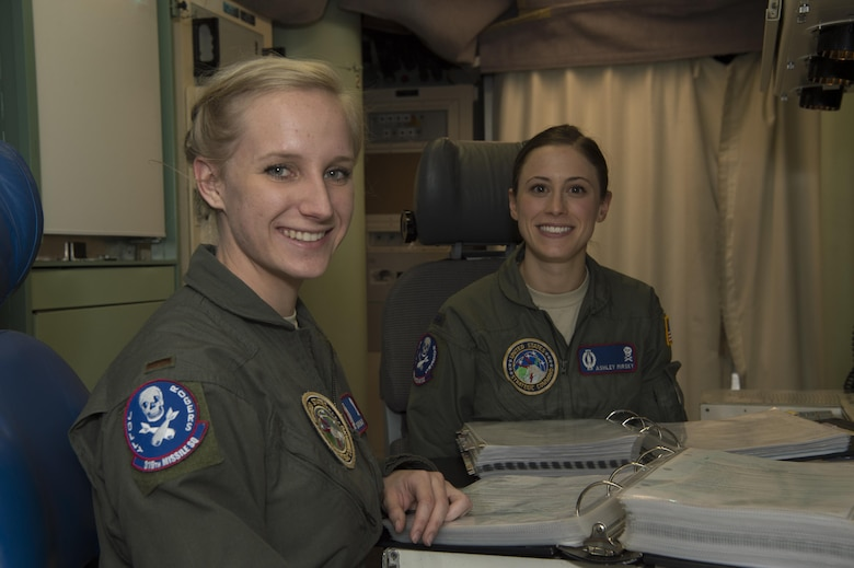 First Lt. Ashley Mirsky, 319th Missile Squadron missile combat crew commander, and 2nd Lt. Marie Blair, 319th MS deputy missile combat crew commander, pose for a photo in a launch control center in the 90th Missile Wing missile complex, Dec. 19, 2016. They have established an effective team dynamic by focusing on the positive attributes each brings to their partnership. (U.S. Air Force photo by 1st Lt. Veronica Perez)