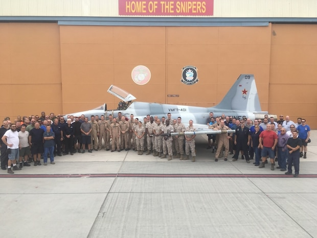 """Marines from Marine Fighter Training Squadron 401 pose for a group photo beside an F-5N Tiger II aboard Marine Corps Air Station Yuma, AZ, October 7, 2016. VMFT-401 is the first and only reserve squadron in the Marine Corps tasked to act as the opposing force in simulated air combat. The """"Snipers"""" study and mimic the tactics of enemy forces to accurately reproduce what the pilots will face in a warfare environment. Now, the Snipers are training the pilots of the Marine Corps' newest aircraft, the F-35. (U.S. Marine Corps Photo by Capt. Samuel L. Baumer)"""