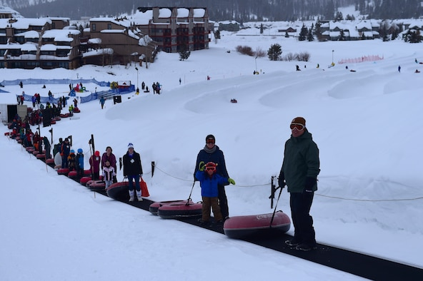 SnoFest attendees ride a conveyer belt to the top of the tubing hill Jan. 21, 2017, at Copper Mountain, Colo. SnoFest included family events such as a tubing hill, a cardboard sled derby and a buffet dinner. (U.S. Air Force photo by Airman Jacob Deatherage/Released)
