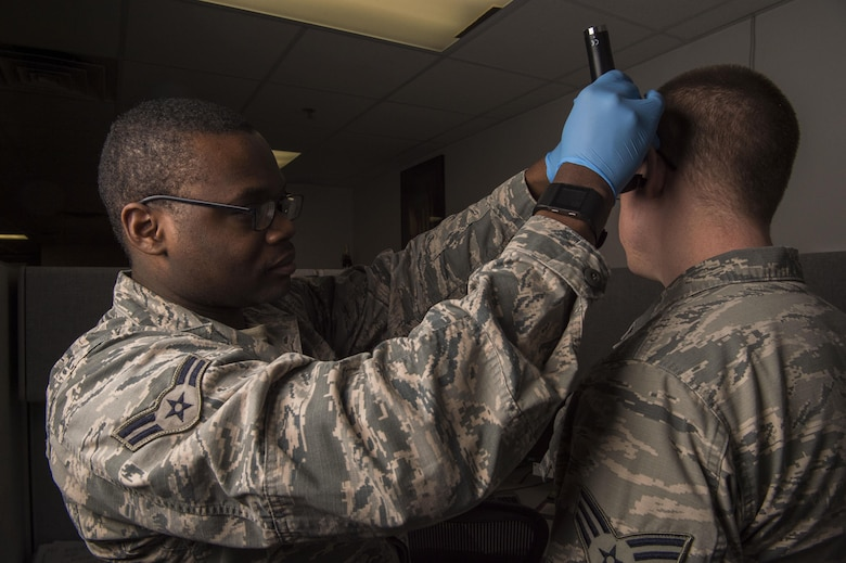 Airman 1st class Alvin Daniels, 90th Medical Operations Squadron public Health technician, performs a lighted ear inspection on a patient at F.E. Warren Air Force Base, Wyo., Jan. 20, 2017. The Air Force celebrates Biomedical Science Corps Appreciation Week Jan. 23 to 27. The Biomedical Science Corps is comprised of 15 medical Air Force Specialty Codes of which 10 are represented at F.E. Warren. (U.S. Air Force photo by Staff Sgt. Christopher Ruano)