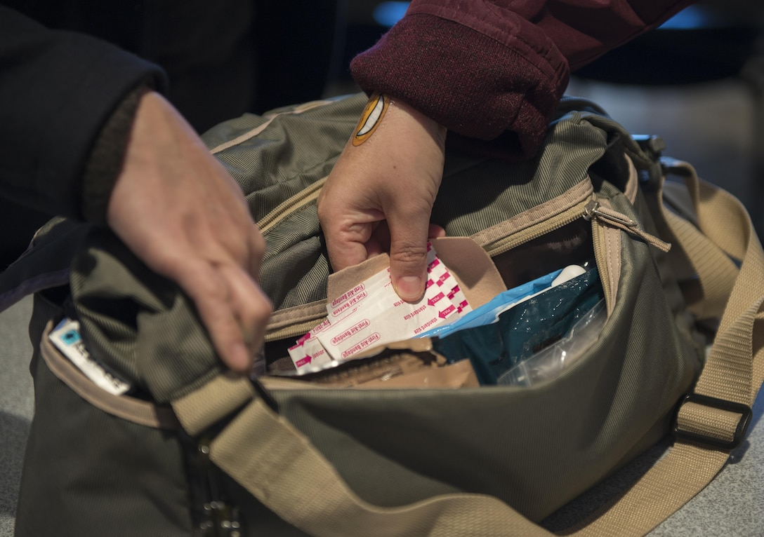 Participants of a Noncombatant Evacuation Operation Townhall meeting inspect the contents of a NEO kit, a bag used to carry documentation, rations, medication and other essentials in case of an immediate disaster or evacuation, Jan. 23, 2017, at Yokota Air Base, Japan. NEO is a mandatory or voluntary departure of civilian noncombatants and nonessential military personnel from danger in an overseas country. (U.S. Air Force Photo by Airman 1st Class Juan Torres)
