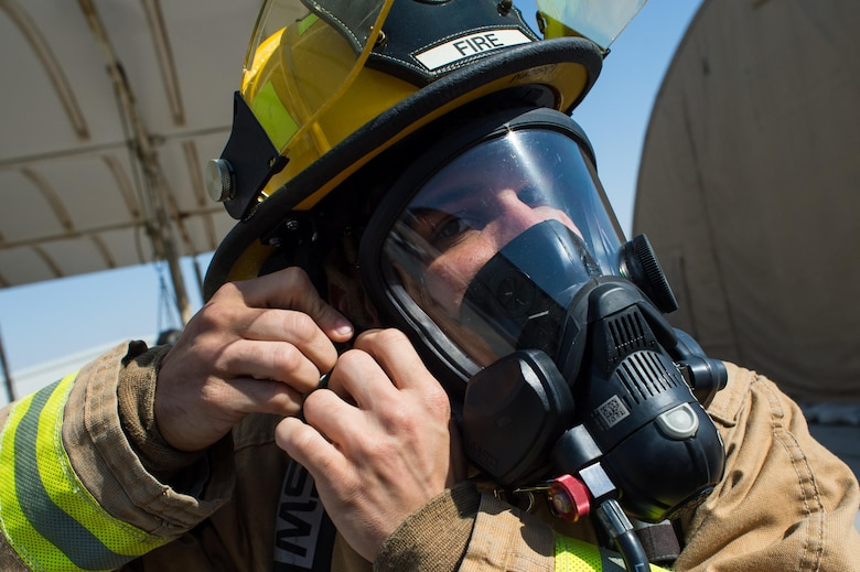 A 380th Expeditionary Civil Engineering Squadron firefighter properly secures his mask before a timed firefighter confidence course at an undisclosed location in Southwest Asia, Jan. 16, 2016. Wearing up to 75 pounds of equipment, participants completed nine stages during the course including a ladder climb, hose drag, sled pull, hose throw, equipment carry, forcible entry, hotel pack, equipment hoisting and rescue. (U.S. Air Force photo/Senior Airman Tyler Woodward)